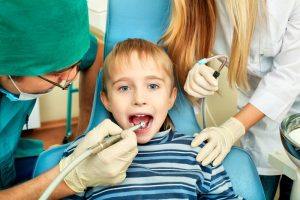 boy getting his tooth removed by the dentist picture
