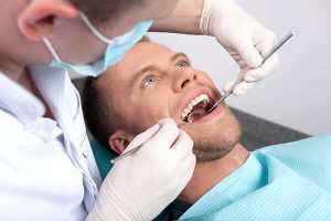 dentist removing tooth from a patient photo