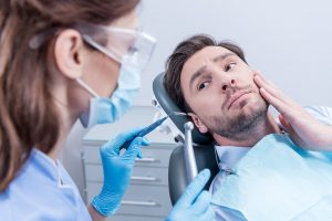 dental patient showing where he is having tooth ache photo